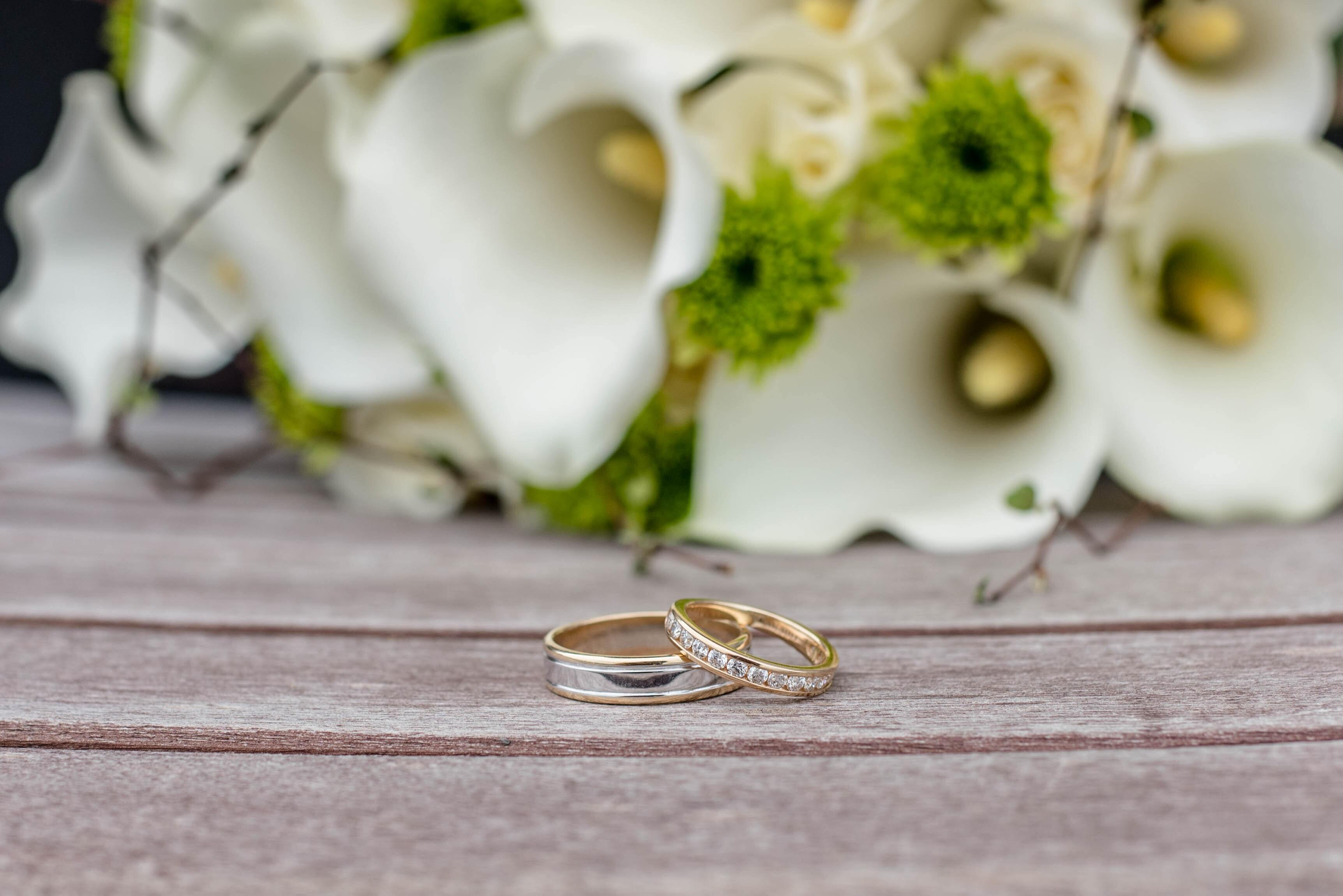 Wedding rings in front of flowers